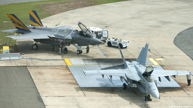A Navy F-35C and the plane it will replace, the F/A-18E Super Hornet, sit together on a runway.