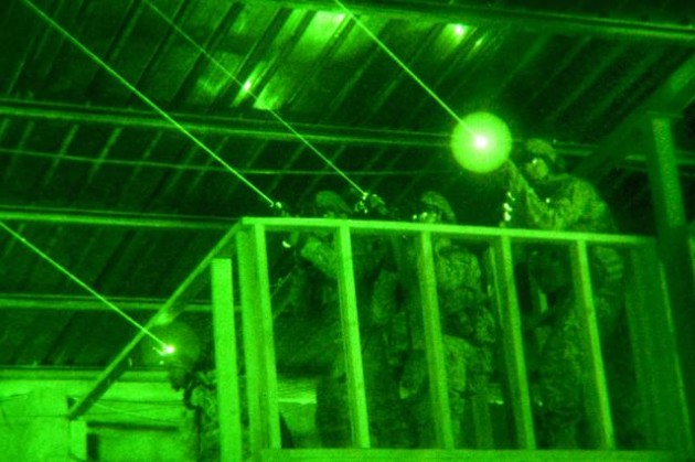 Army soldiers training with laser sights and night vision devices.