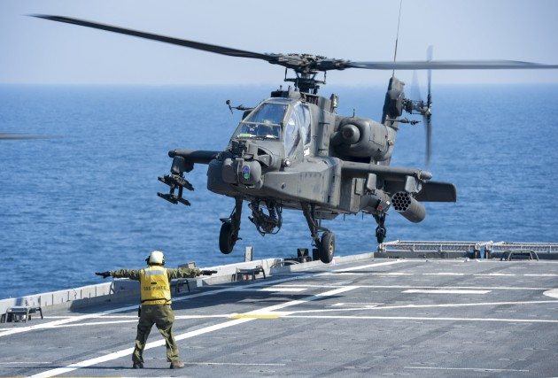 A US Army Apache helicopter lands on a Navy ship in the Persian Gulf region.