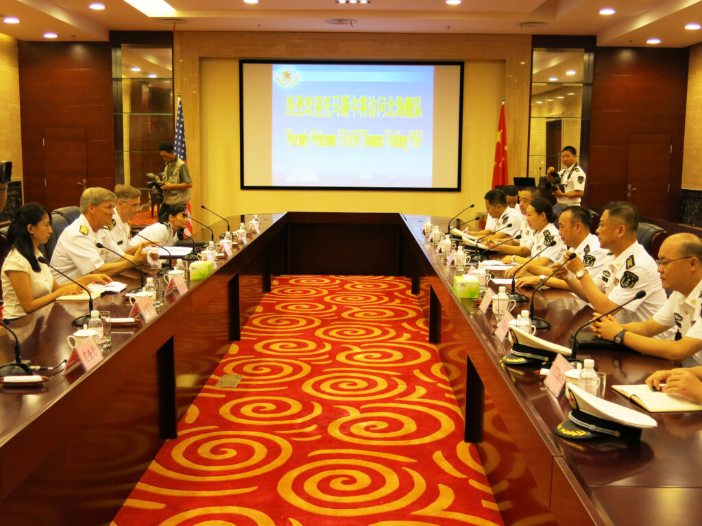 Navy officers from the US (left) and China (right) meet in Qingdao on Monday.