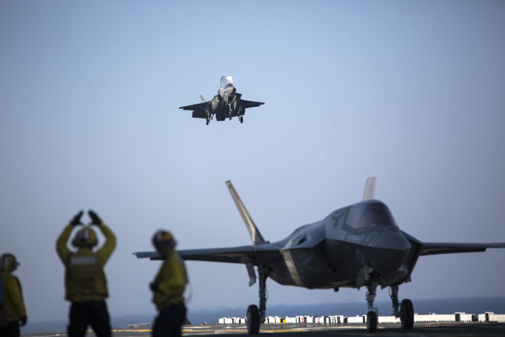 A sailor aboard the USS Wasp (LHD-1) signals to the pilot of an F-35B Lightning II Joint Strike Fighter to land as it arrives for the first phase of operational testing, May 18, 2015.  The short take-off, vertical landing capabilities of the F-35B are crucial to the mission of the Marine Corps and necessary for operation aboard a Navy amphibious ship. The aircraft are stationed with Marine Fighter Attack Training Squadron 501, Marine Aircraft Group 31, 2nd Marine Aircraft Wing, Beaufort, South Carolina and Marine Fighter Attack Squadron 121, Marine Aircraft Group 13, 3rd Marine Aircraft Wing, Yuma, Arizona. (U.S. Marine Corps photo by Lance Cpl. Remington Hall/Released)