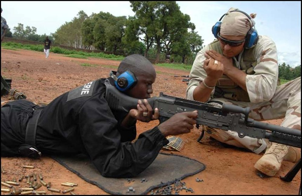 A Navy sailor instructs a Malian police officer